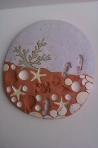 Making impressions into clay and slip painted.  Bisque fired by Carol Havard