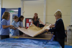 Ringmer Primary School  pupils lifting the mosaic very carefully as it is stuch to the bottom of the brown paper